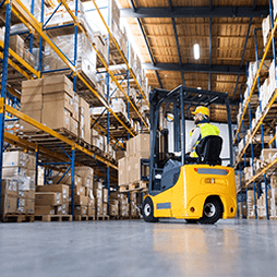 business - forklift operator lifting boxes in a warehouse