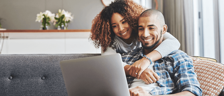 couple smiling looking at laptop